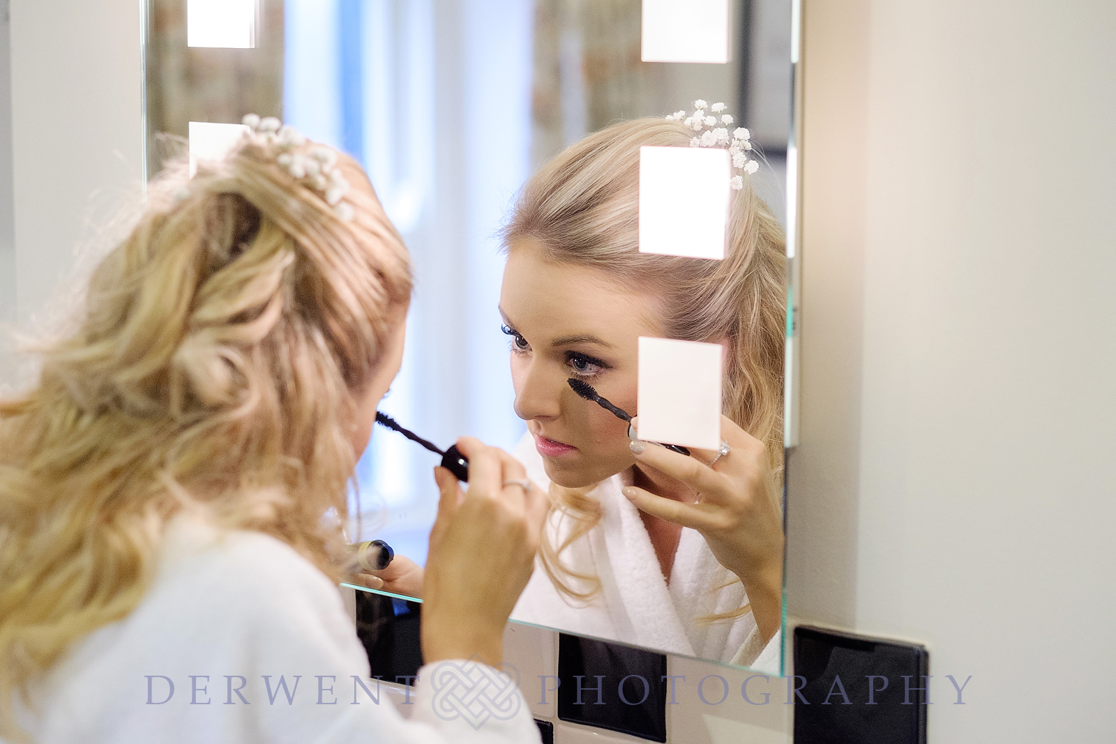 Bride reflected in morror applying makeup