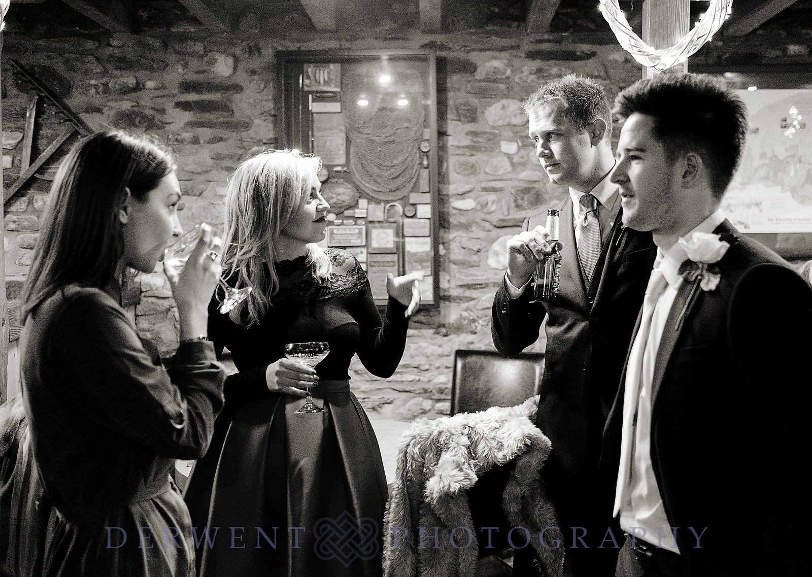 bw photograph of wedding guests in the barn