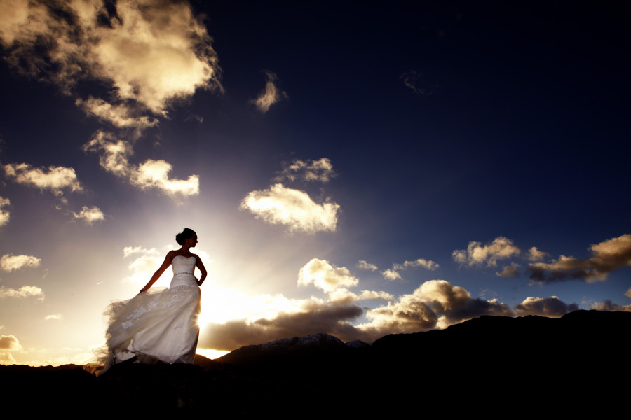 bride silhouetted against dramatic winter skies in Langdale on her wedding day