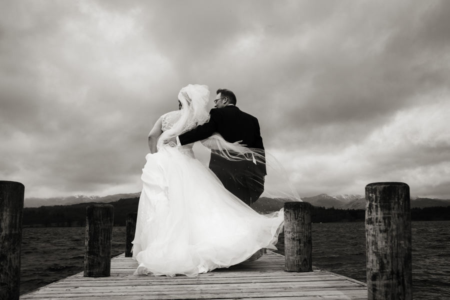 wedding couple on the lowwood bay jetty, windermere on a wild and windy day