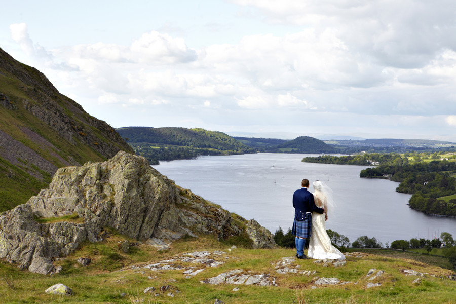 BRIDE AND KILTED GROOM LOOKING OVER ULLSWATER FROM HOWTOWN AFTER THEIR SHARROW BAY WEDDING