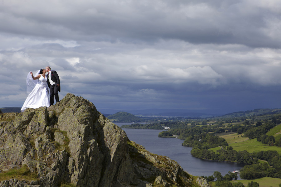 brides veil blowing in the wind as she stands with her groom on a crag overlooking ullswater after being married at another place.
