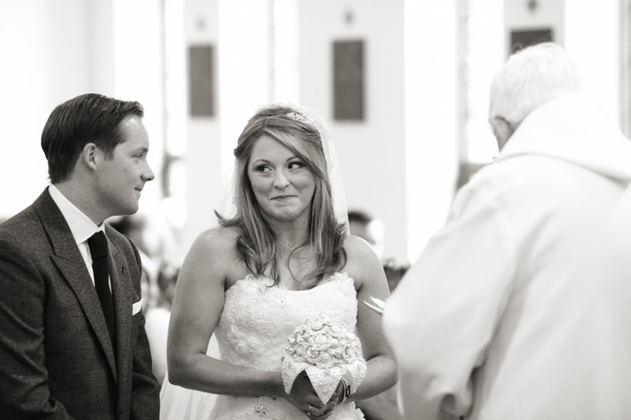 the look of love between bride & groom during their wedding ceremony in grasmere church
