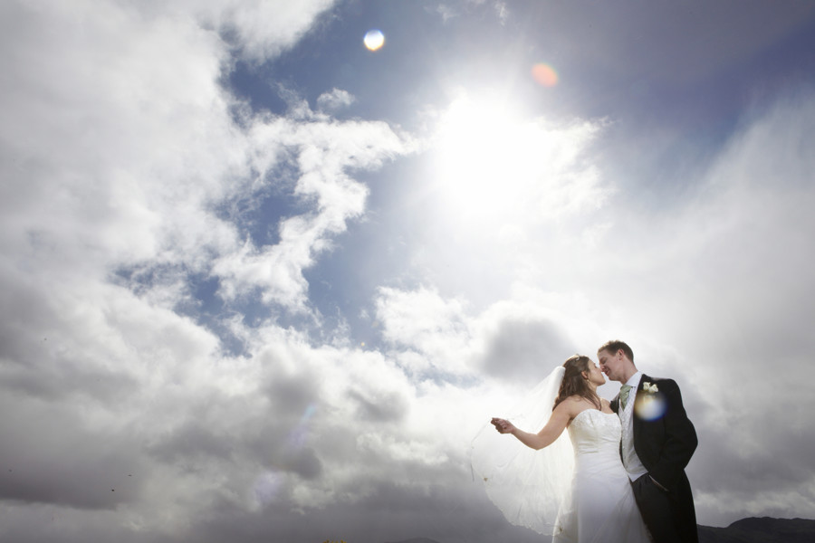 groom and his bride in the langdale valley with sun and clouds behind