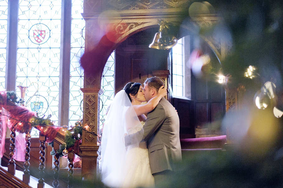 bride & groom kiss after wedding vows shot through xmas decorations in the langdale chase hotel, windermere