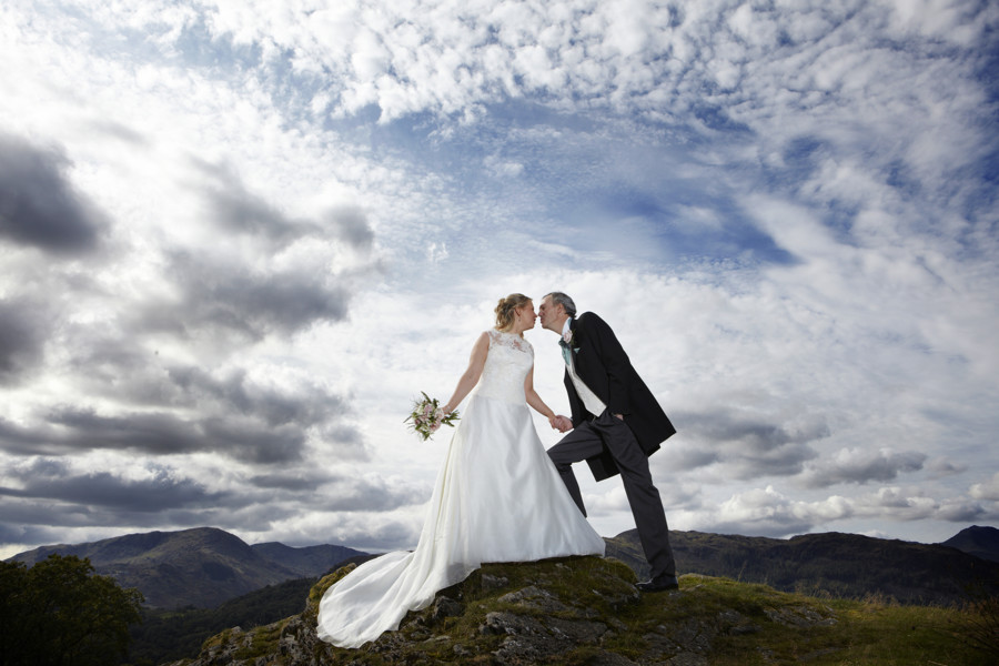 blue sky and dramatic clouds behind bride & groom posing for photographs in front of the langdale pikes