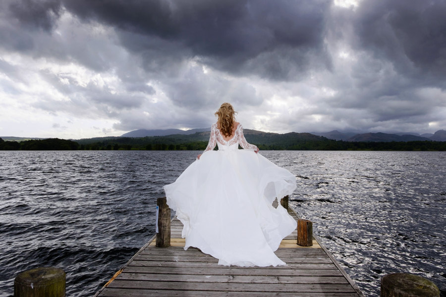 windswept bride on the jetty of the lowwood botel looking at a wild windermere