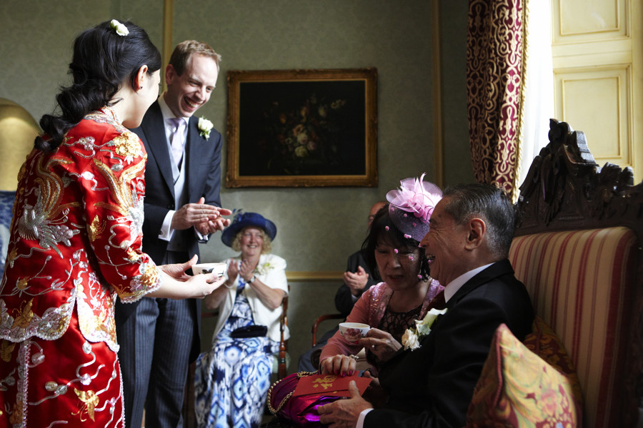 bride serves mother in chinese tea ceremony as groom looks on before their wedding at storrs hall