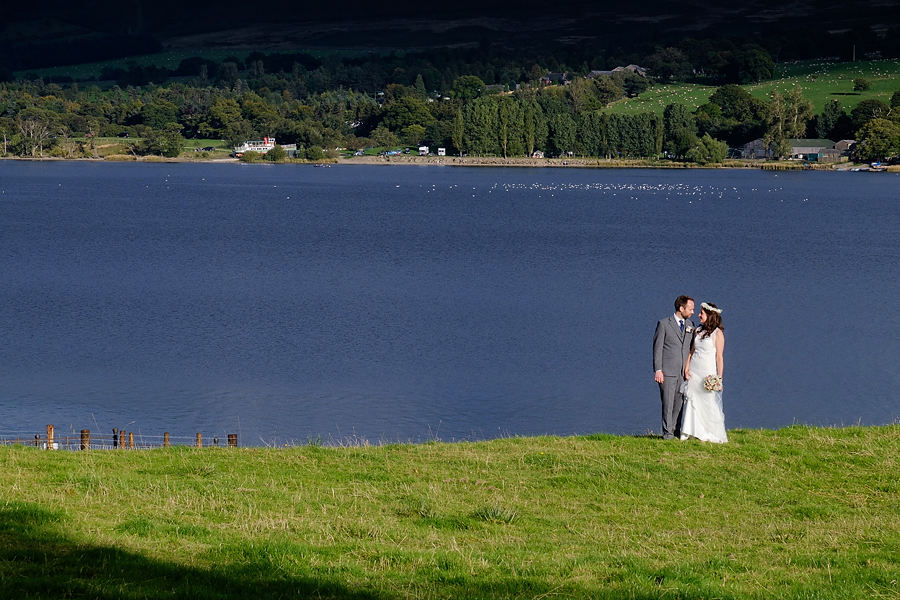 bride & Groom by the shores of ullswater in the lake district on their wedding day