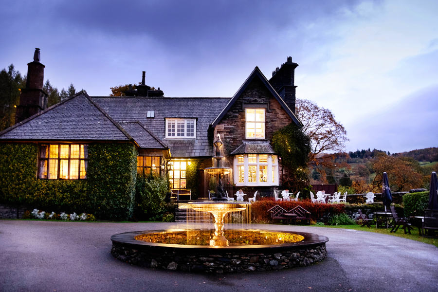 lake district wedding venue braodoaks hotel and it's fountain lit up at night.