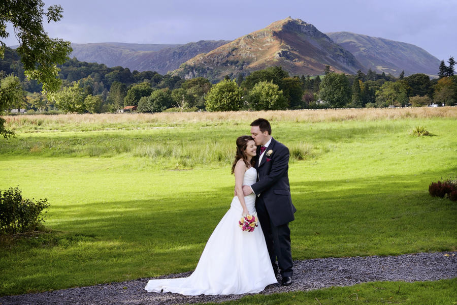 bride & groom with lake district mountains behind at the daffodil hotel, a grasmere wedding venue