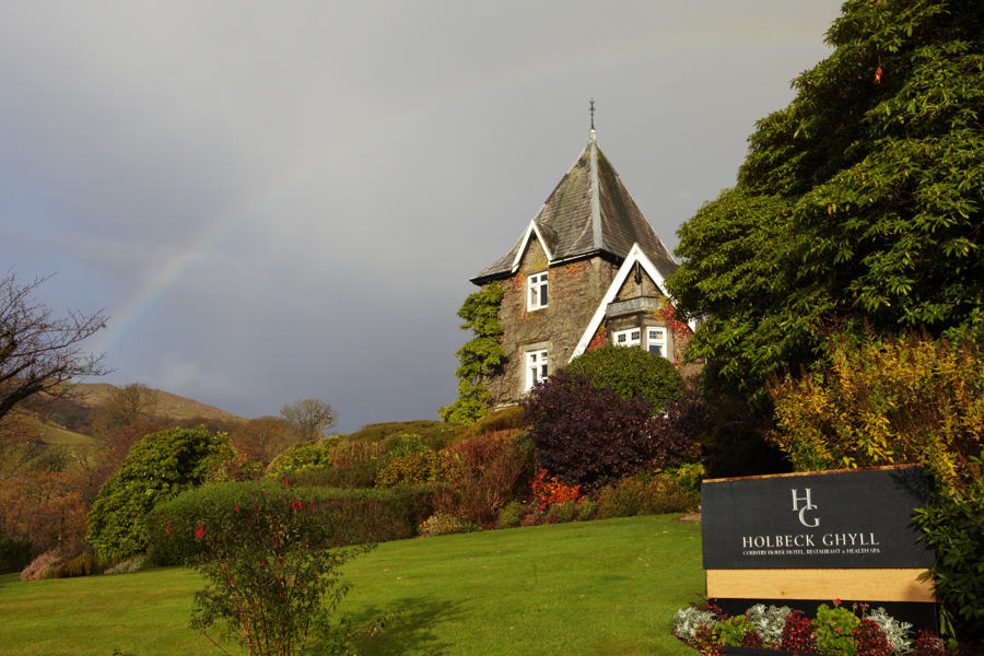 a rainbow arcs across Holbeck Ghyll Hotel, a lake district wedding venue high above windermere