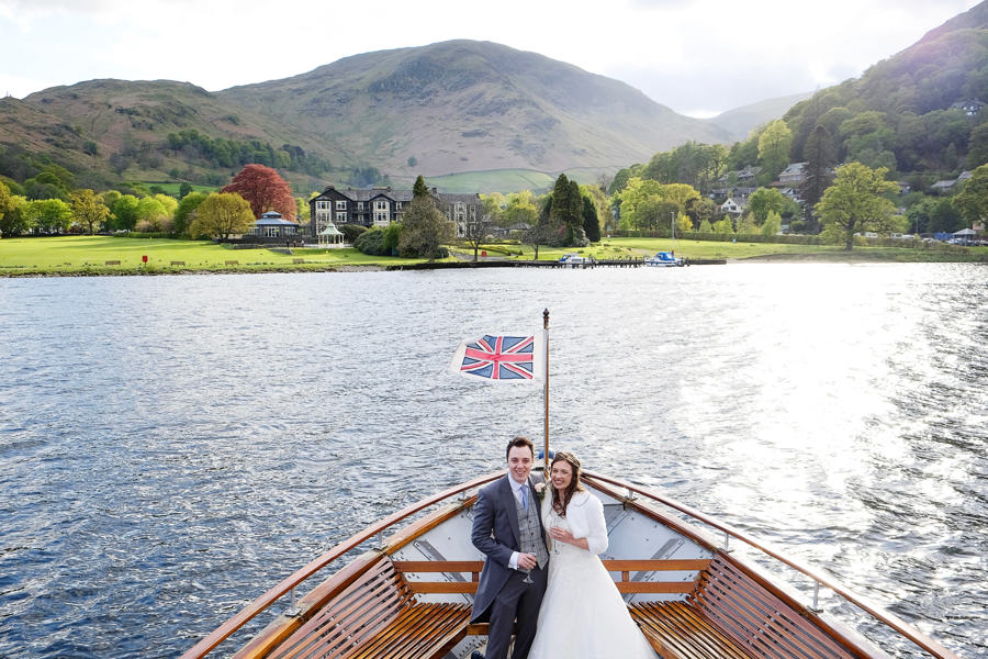 popular lake district wedding venue the Inn on the Lake from Ullswater, with bride and groom posing at front of lake stamer