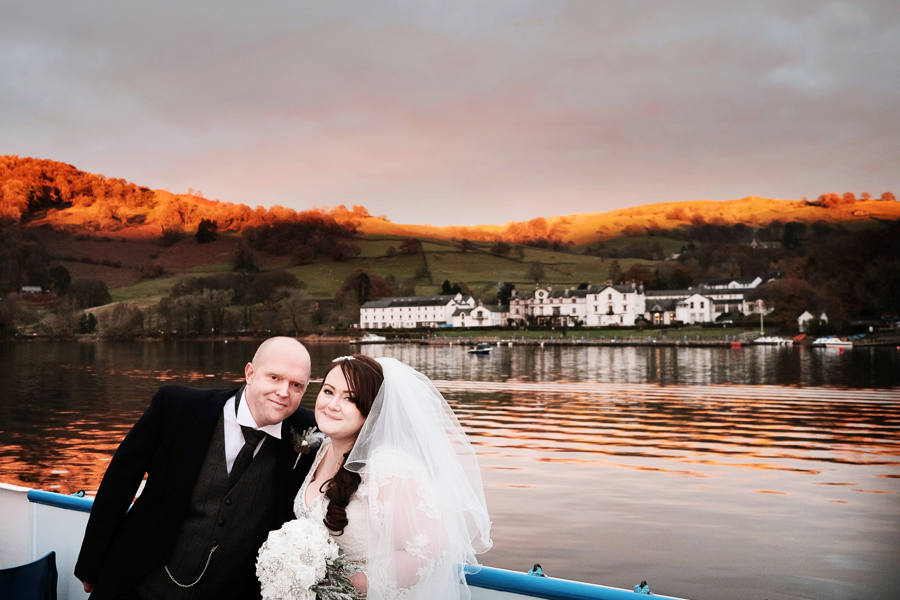 bride and groom on windermer lake cruise with wedding venue behind
